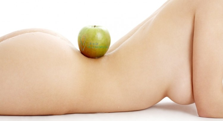 naked woman torso with green apple over white